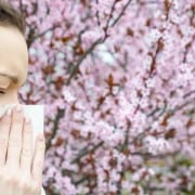Woman blowing nose with flowers in background.