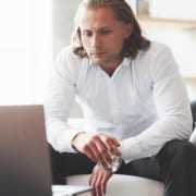 Man looking at laptop with drink in his hand.
